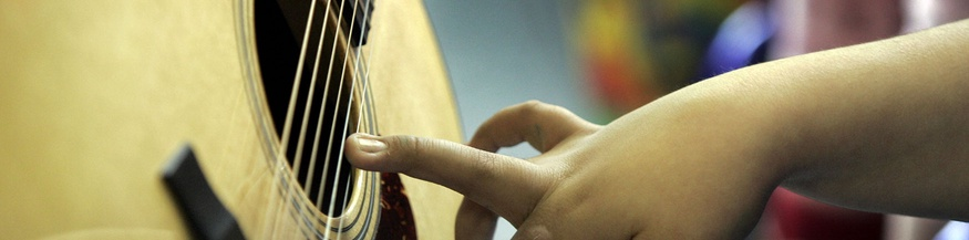 Kind greift nach Gitarrensaiten