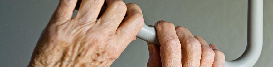 Hände einer alten Frau an einer Haltestange