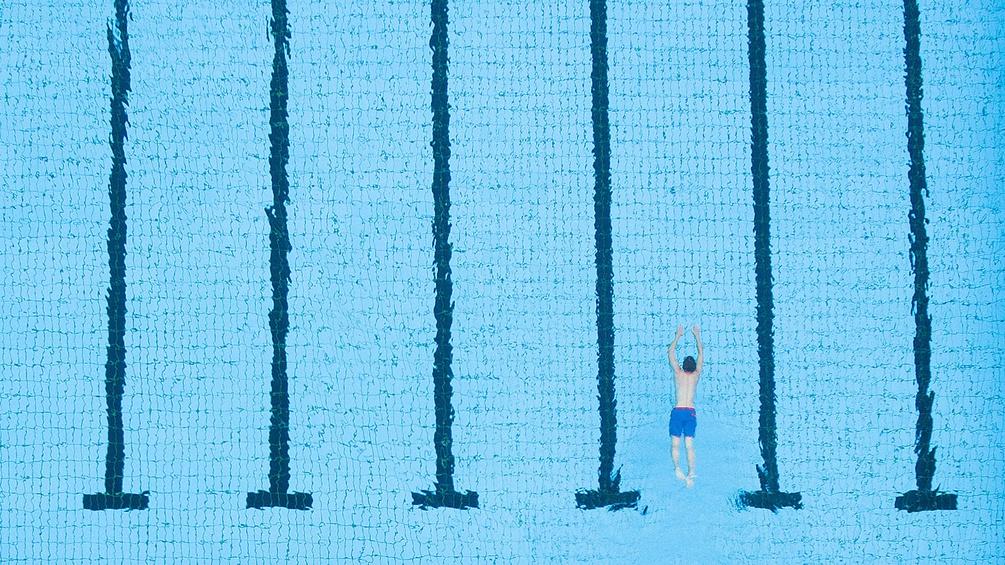 Mann schwimmt im Schwimmbecken
