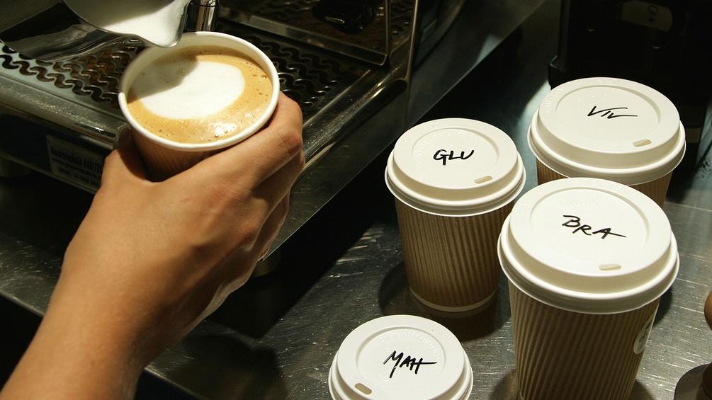 Kaffee wird in Becher gegossen, Deckel beschriftet