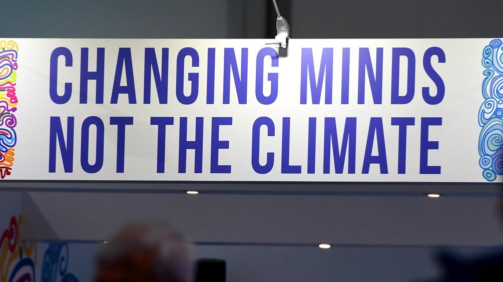 """Ein Plakat auf dem """"Changing MInds, not the Climate"""" steht"""