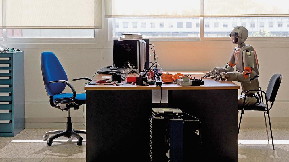 Roboter sitzt am Schreibtisch