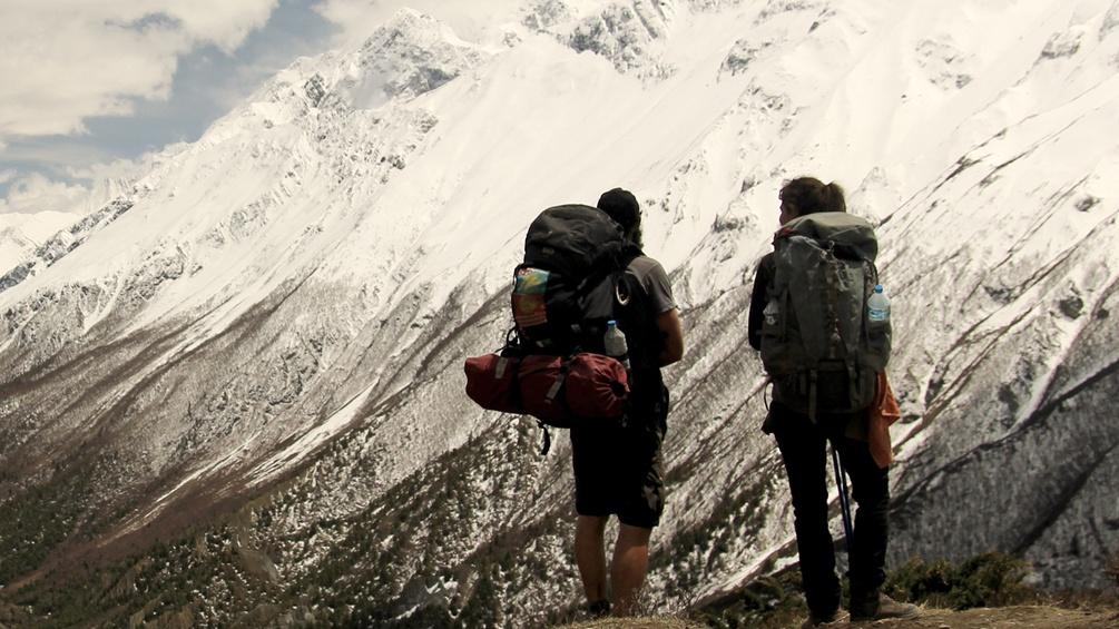Zwei Wanderer vor einem schneebedeckten Gebirgsmassiv