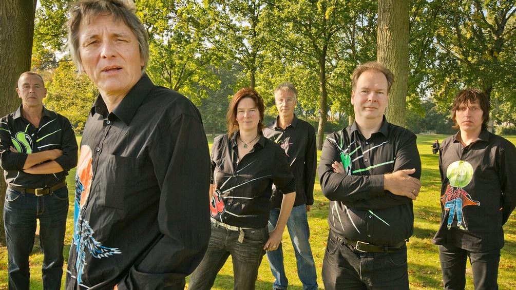 Fünf Männer und eine Frau posieren im Park