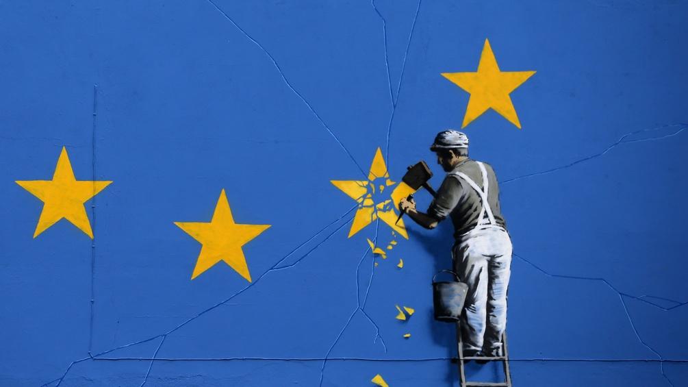 Ein Bild auf einer Hauswand, auf dem ein Mann die Sterne aus dem EU-Banner meißelt