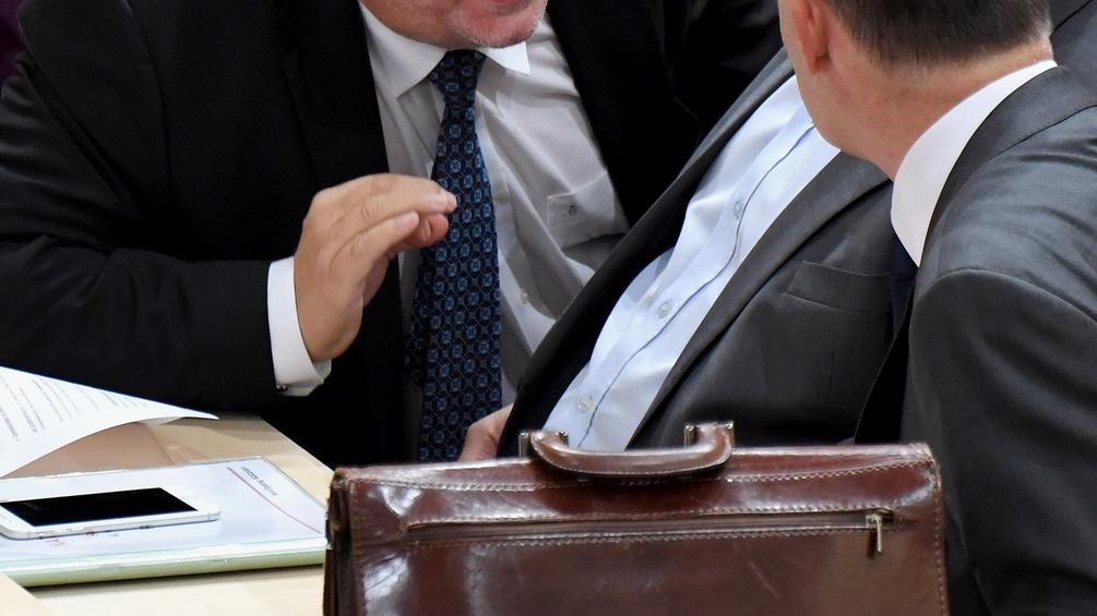 Nationalratsabgeordnete unterhalten sich, Ledertasche