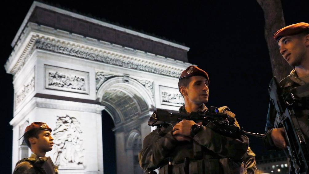 Polizisten vor dem Pariser Triumphbogen nahe der Champs-Elysees
