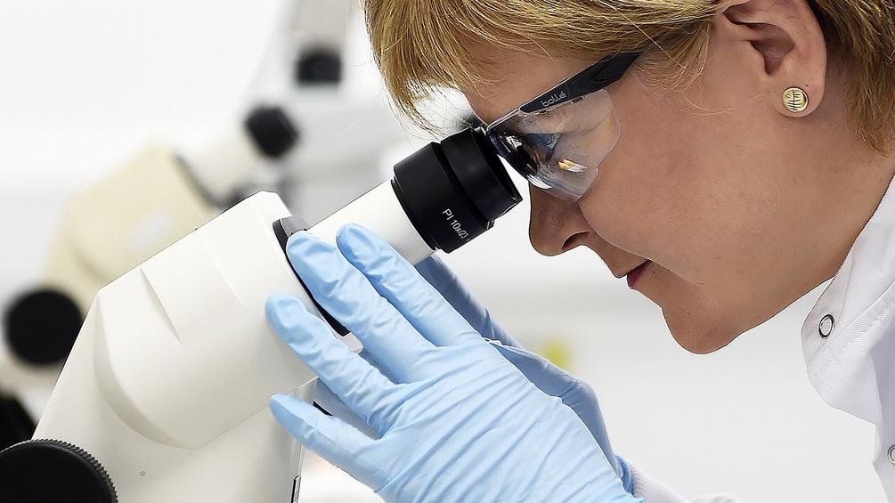 Forscherin blickt ins Mikroskop