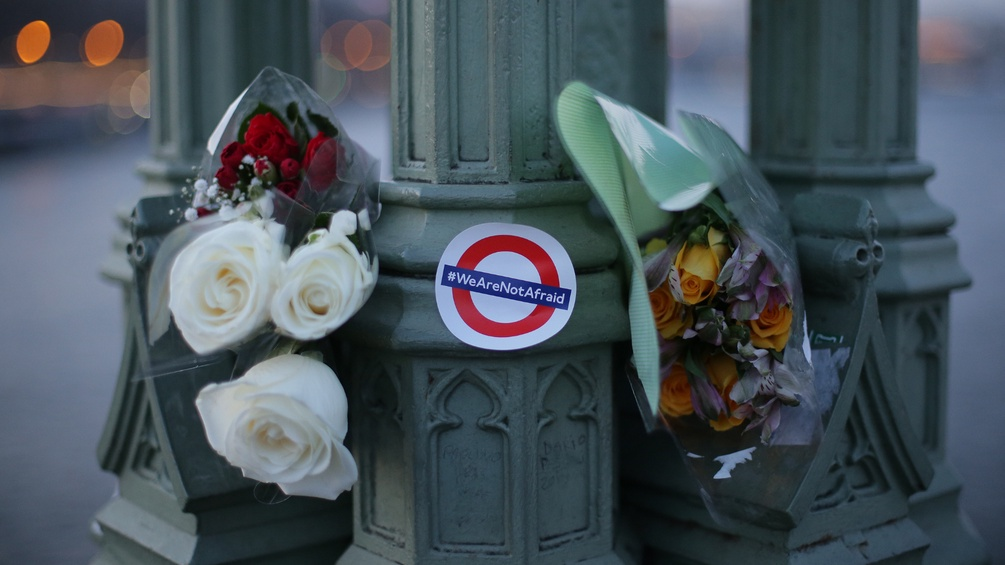 """Blumen und Aufkleber mit dem Logo der Londoner U-Bahn mit der Aufschrift """"We are not afraid"""""""
