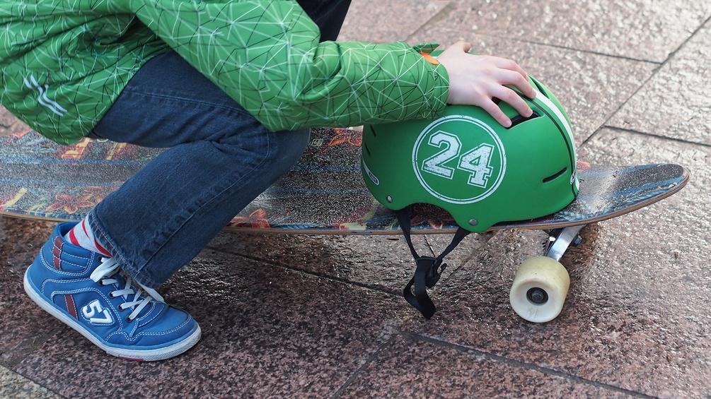Bub mit Skateboard und Helm
