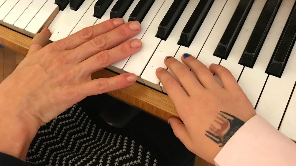 Hände an einer Klaviertastatur
