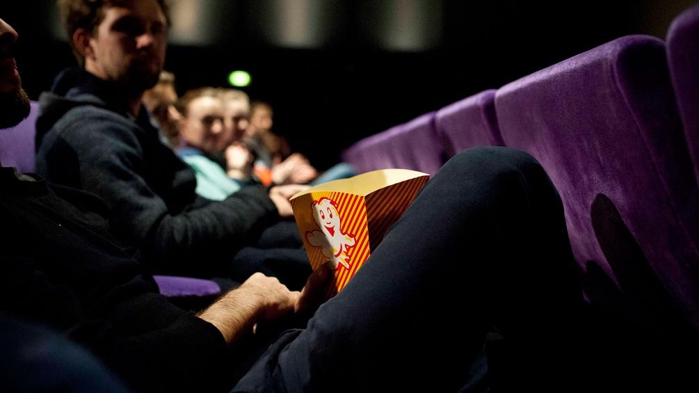 Menschen im Kino mit Popcorn