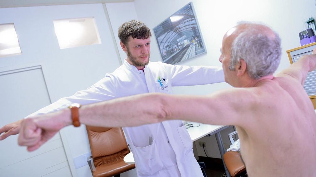 Arzt untersucht Muskeln eines Patienten