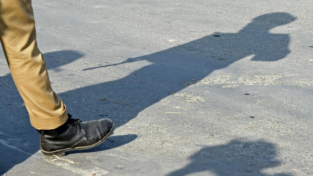 Schatten und Bein eines Soldaten mit Gewehr
