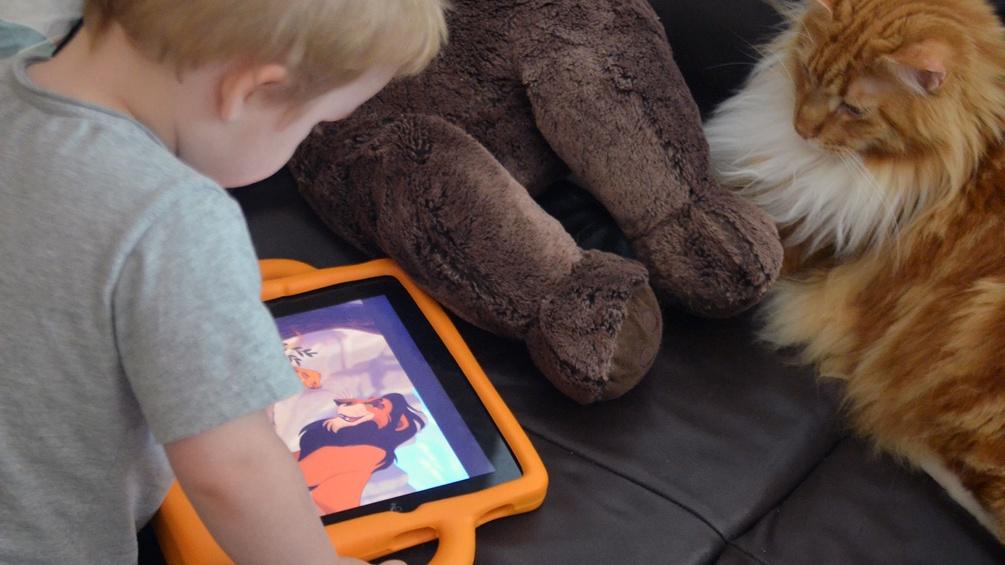 Kind mit iPad, Teddybär und Katze