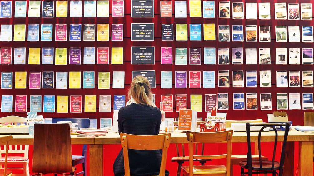 Frau sitz vor einer Bücherwand