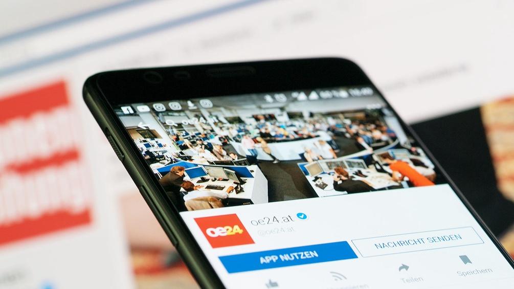 Handy vor Bildschirm, Krone und oe24