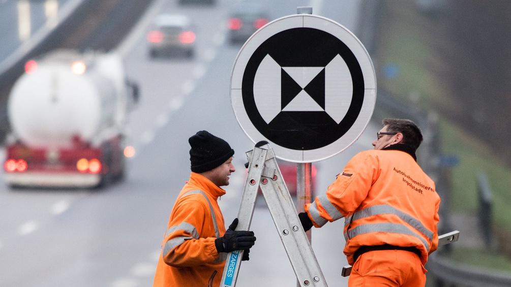 Arbeiter beim Montieren eines Verkehrsschilds
