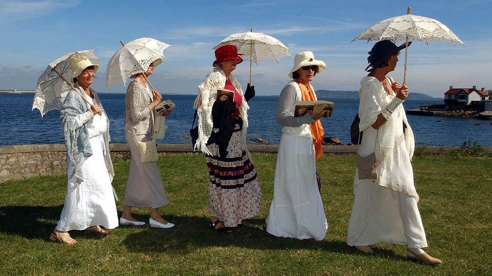 Fünf verkleidete Damen mit Büchern und Sonnenschirmen