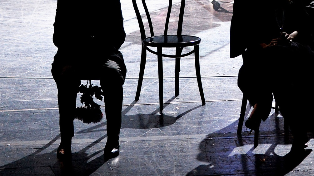Menschen sitzen auf Sesseln auf einer Bühne