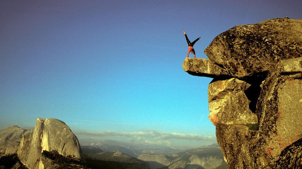 Ein Extremkletterer macht einen Handstand auf einem Felsvorsprung