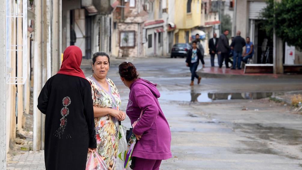 Frauen auf der Straße, im Hintergrund Männer in einer tunesischen Stadt