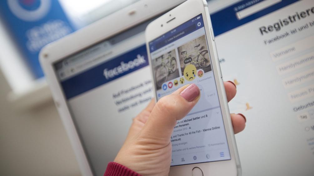 Frau hält Handy in der Hand vor Laptop-Screen