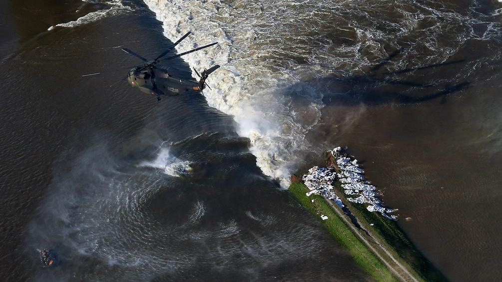 Hubschrauber über einem Dammbruch an der Elbe