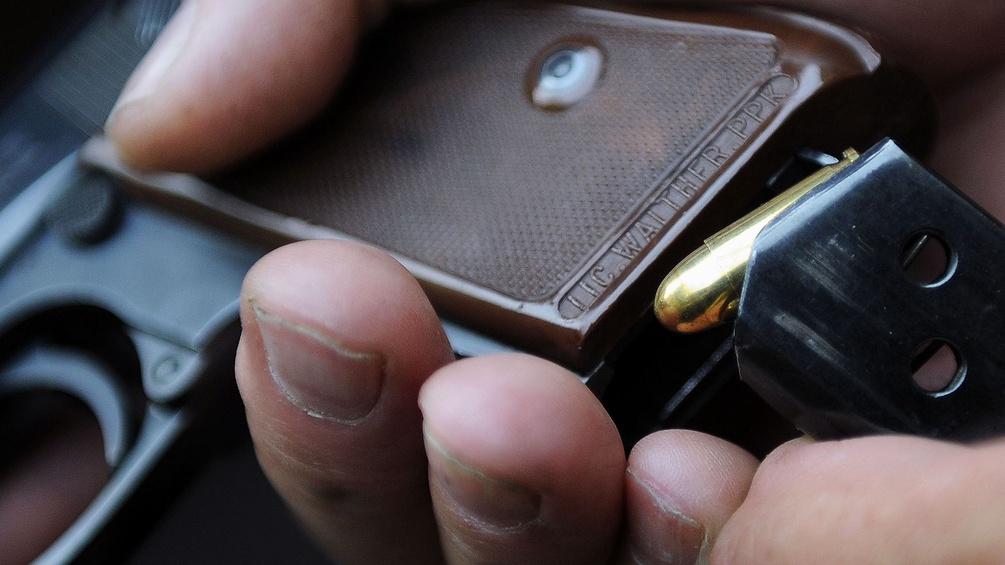 Eine Person ladet eine Pistole