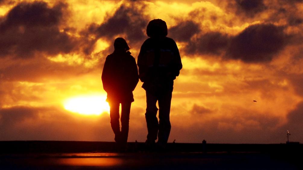 Zwei Menschen spazieren in den Sonnuntergang