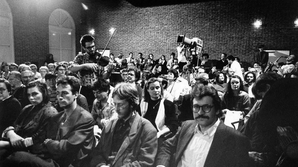 Peter Oswald beim Abschlusskonzert des von ihm programmierten musikprotokoll 1989 neben dem Komponisten Gerd Kühr sitzend)