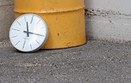 Uhr lehnt an einer gelben Tonne