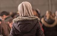 Flüchtlingsfrau mit braunem Kopftuch, von hinten