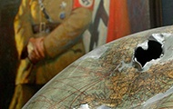 Angeschossene Weltkugel vor einem Hitler-Gemälde (Teil einer Ausstellung)