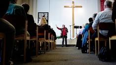 Evangelische Freikirche, Frau steht vor Kreuz und spricht