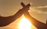 Zwei Hände, die sich halten, im Sonnenuntergang