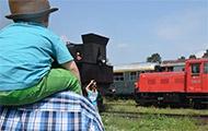 Kind sitzt auf den Schultern, schaut Züge an