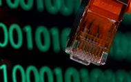 Netzwerkkabel vor einem Computerbildschirm mit dem binären Zahlencode