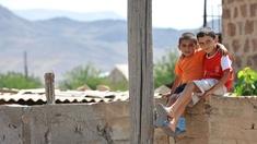 Kinder sitzen auf einer Mauer