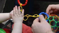 Hände von Kind und Mann mit Spielzeug