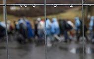 Regentropfen auf einer Absperrung, in der Tiefenunschärfe Menschen