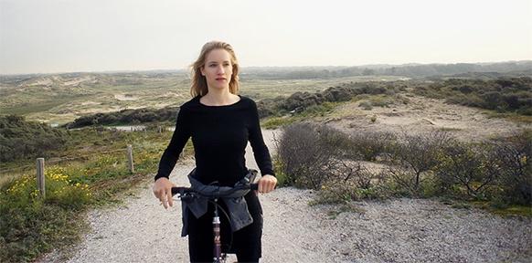 Frau am Strand auf einem Fahrrad