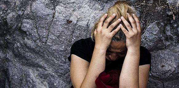 Eine Frau schützt ihren Kopf mit den Händen