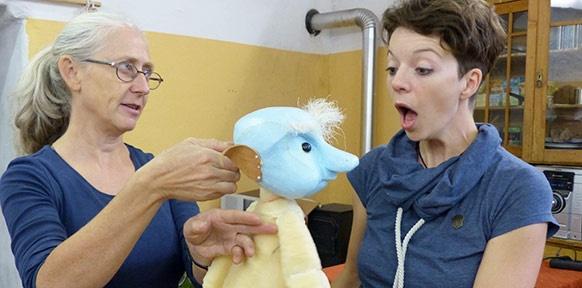 Verwunderte Frau mit Puppe und Künstlerin