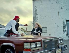 Rapper auf Motorhaube zeigt auf Frau mit blonden Haaren