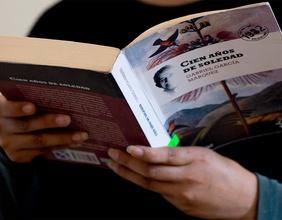 """Eine Frau hält das Buch """"Hundert Jahre Einsamkeit"""" von Marquez in den Händen"""