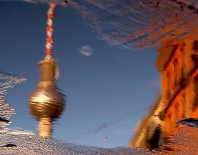 Der Berliner Fernsehturm spiegelt sich in einer Wasserlache