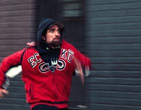 Junger Mann, mit schwarzer Kaputze und roter Jacke, rennt